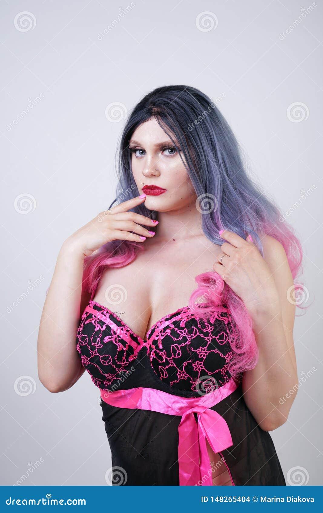 Signora paffuta graziosa sveglia che porta il vestito sessuale dalla biancheria della bamboletta sul fondo bianco dello studio