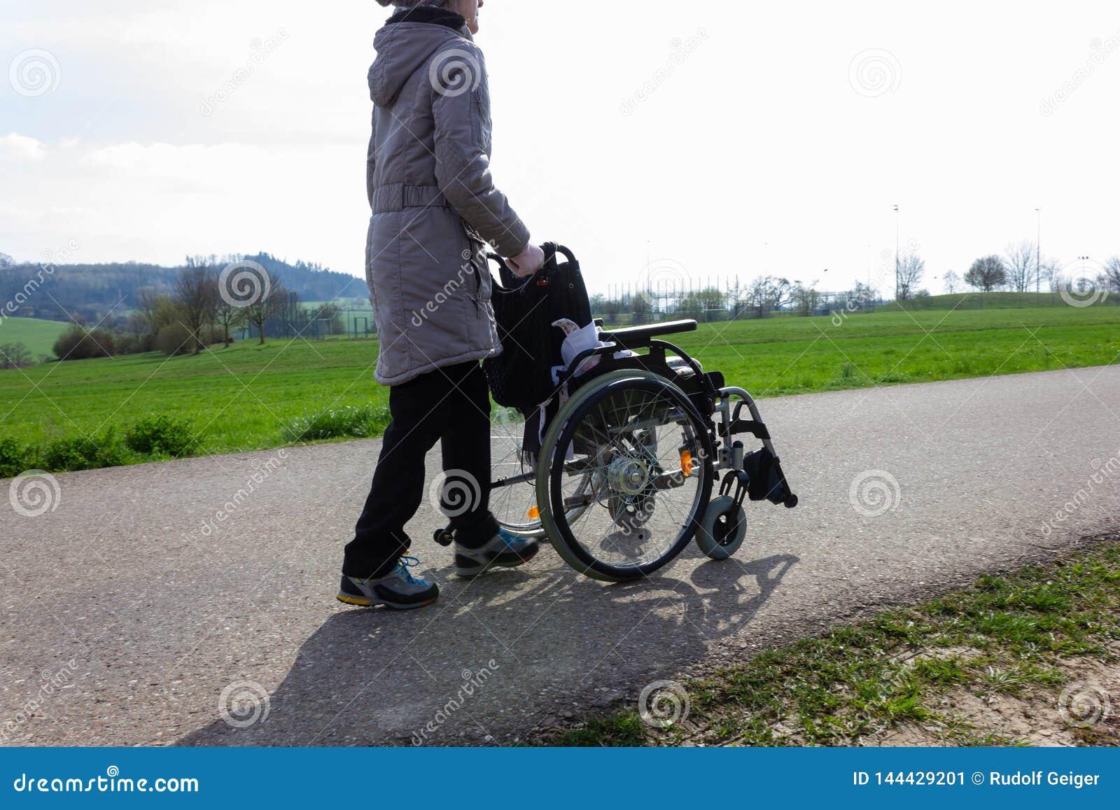 Signora senior che spinge sedia a rotelle