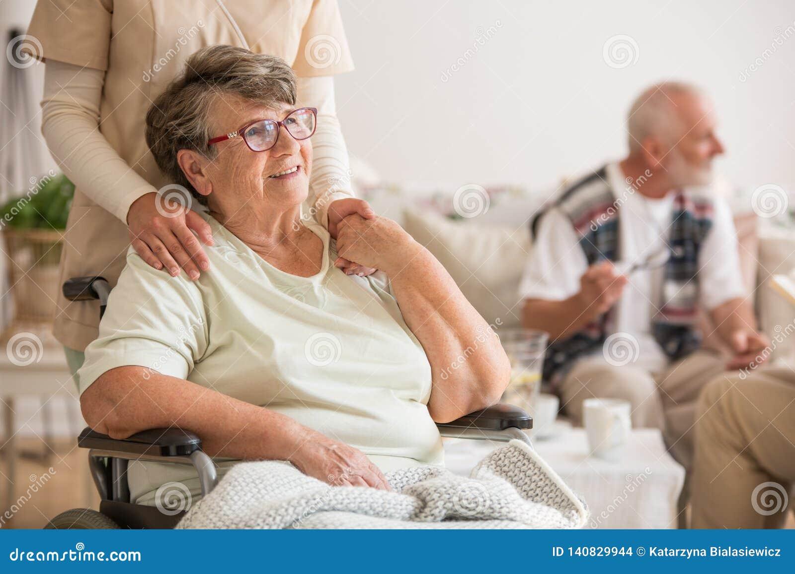 Signora senior felice che si siede alla sedia a rotelle nella casa di cura per gli anziani