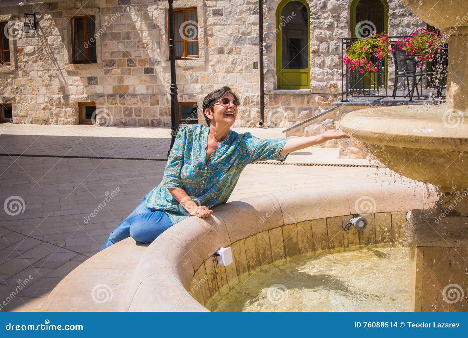 Signora senior sulla fontana