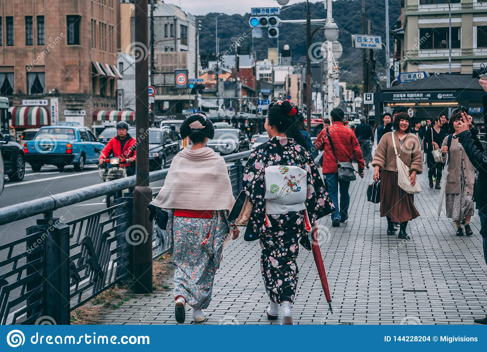 Signore in attrezzature giapponesi tradizionali che camminano le vie di Kyoto