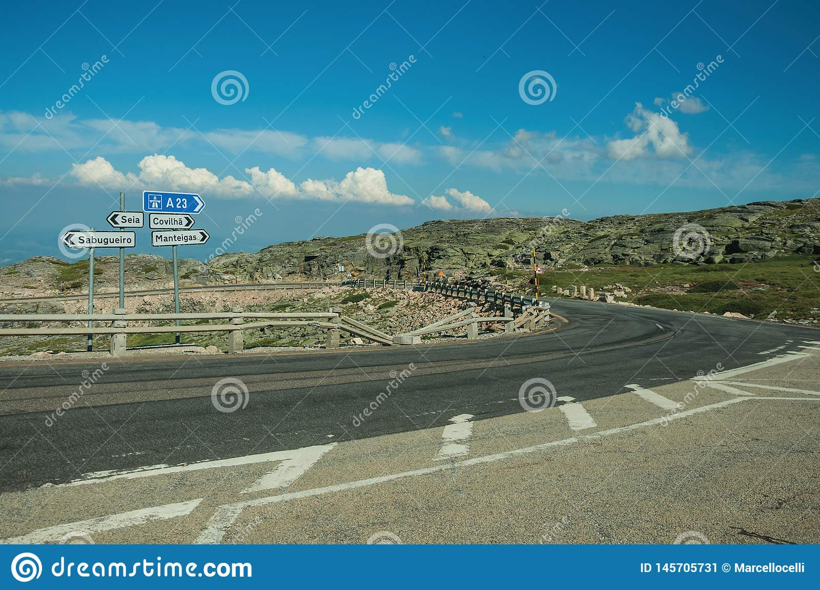 Signposts with town directions on road crossing rocky landscape