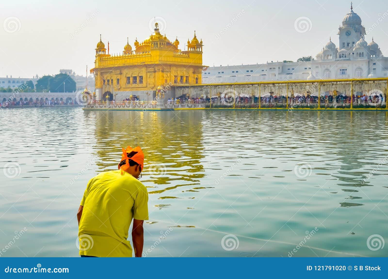 Sikhijski pielgrzymi modlenie w świętym cysternowym pobliskim Złotym Świątynnym Sri Harmandir sahibie, Amritsar, INDIA
