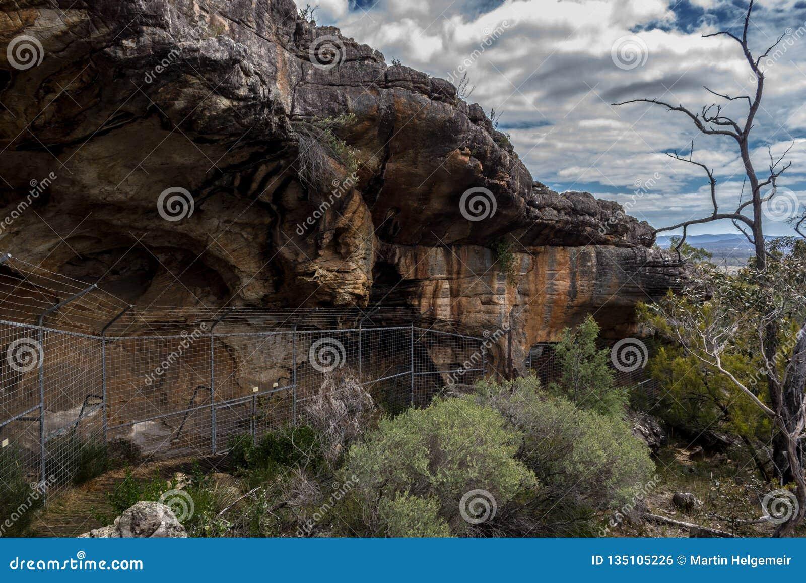 Sikt över en infödd grotta, bak ett staket, i Australien