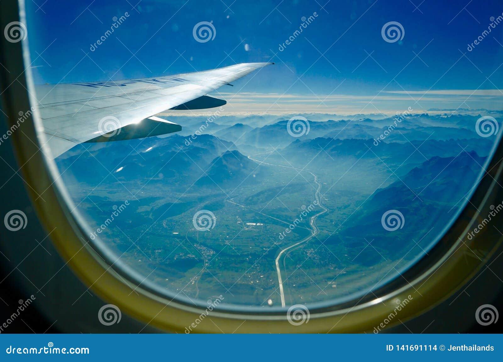 Sikt av berg och dalen från flygplanfönster