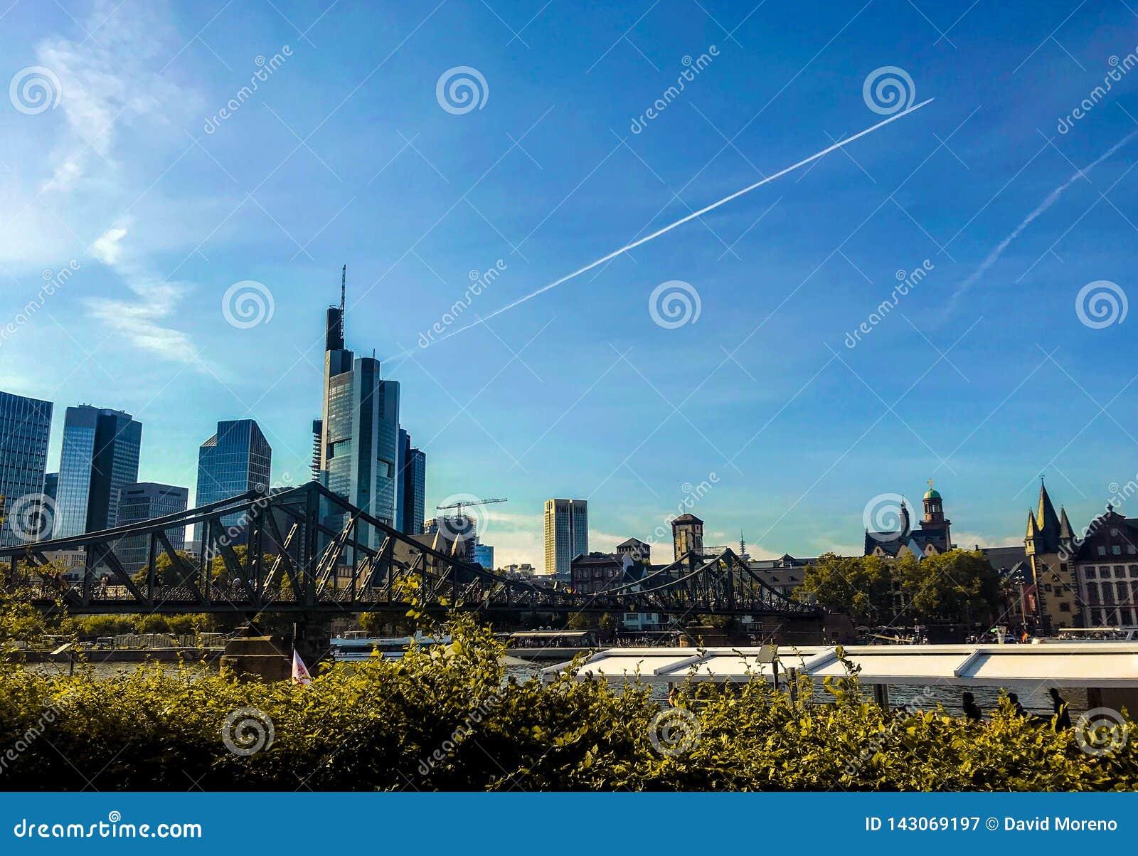 Sikt av bron Eiserner Steg som korsar den huvudsakliga floden mot cityscape av Frankfurt