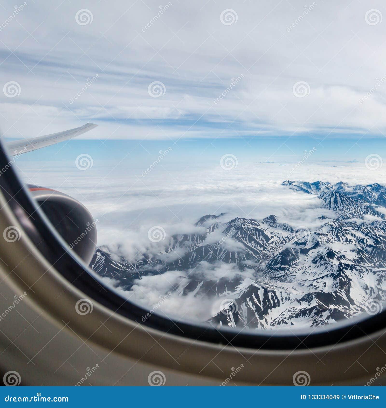 Sikt av de Kamchatka bergen från flygplanhyttventilen