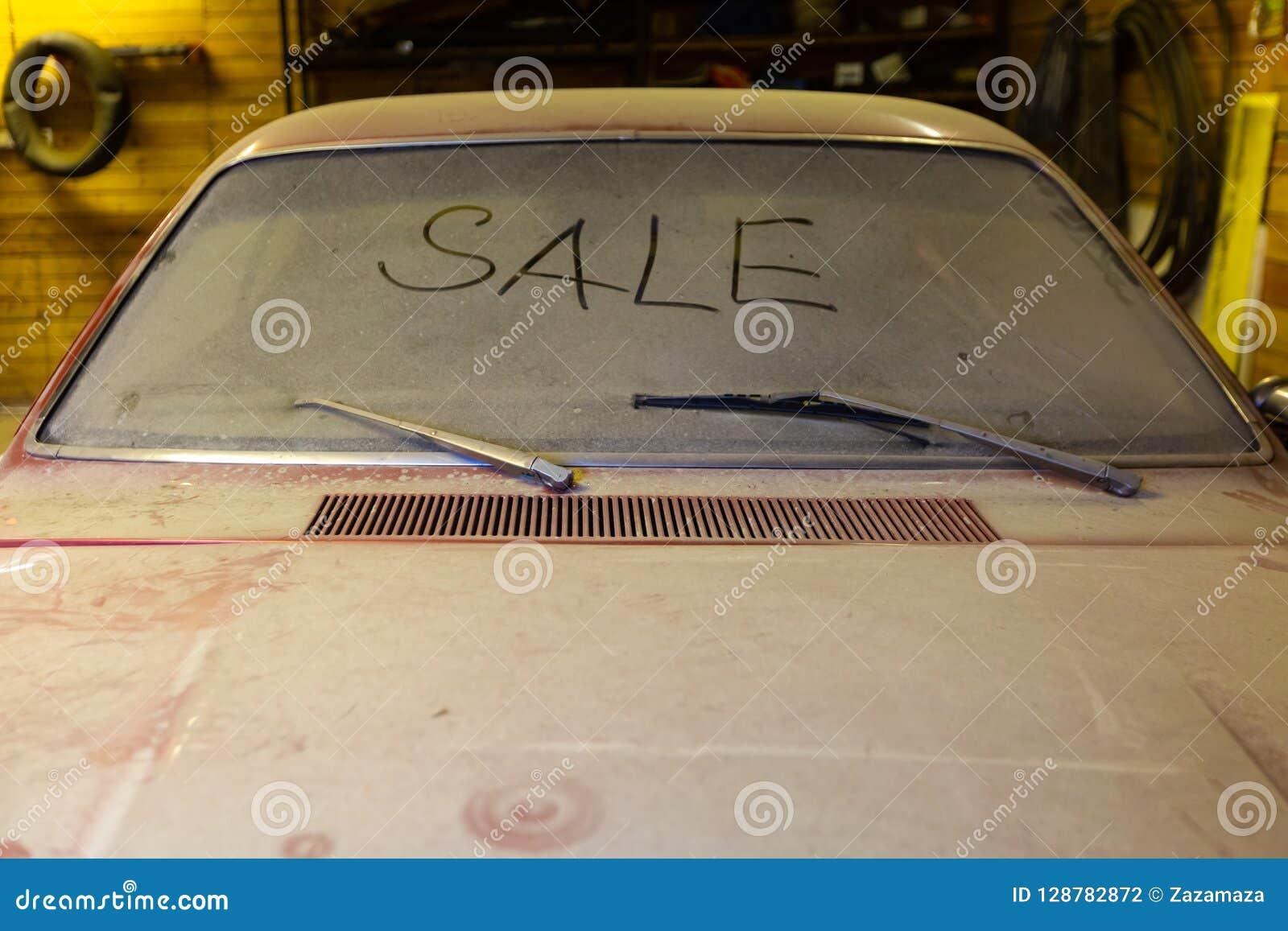 Sikt av den gamla bilen i garage med den smutsiga vindskärmen för dammig huv med titeln SALE vid fingret och bruten vindrutawip
