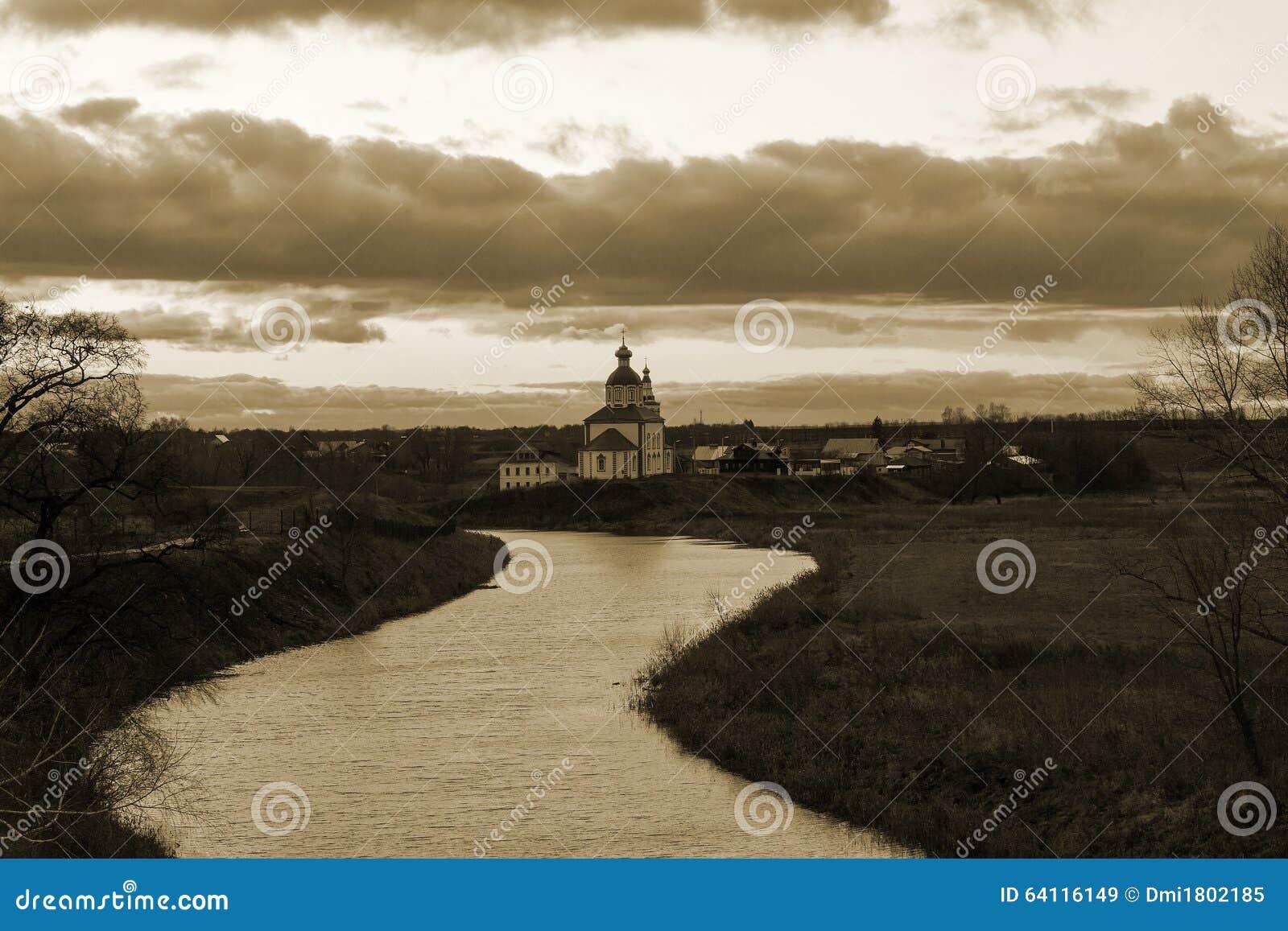 Sikt av den Kamenka floden och kyrkan på solnedgången i sen höst Suzdal Ryssland