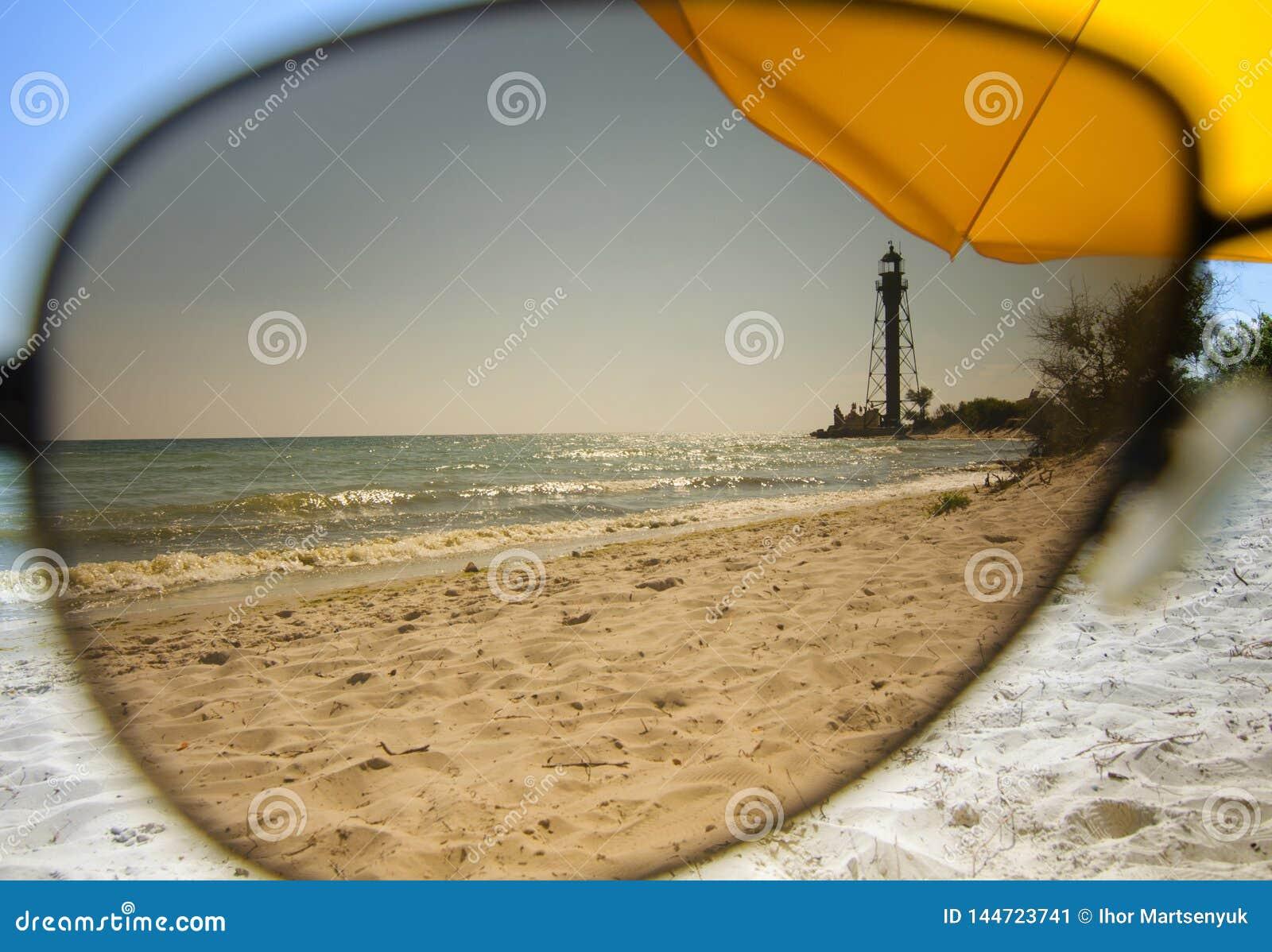 Sikt av den sandiga kusten till och med solglasögon