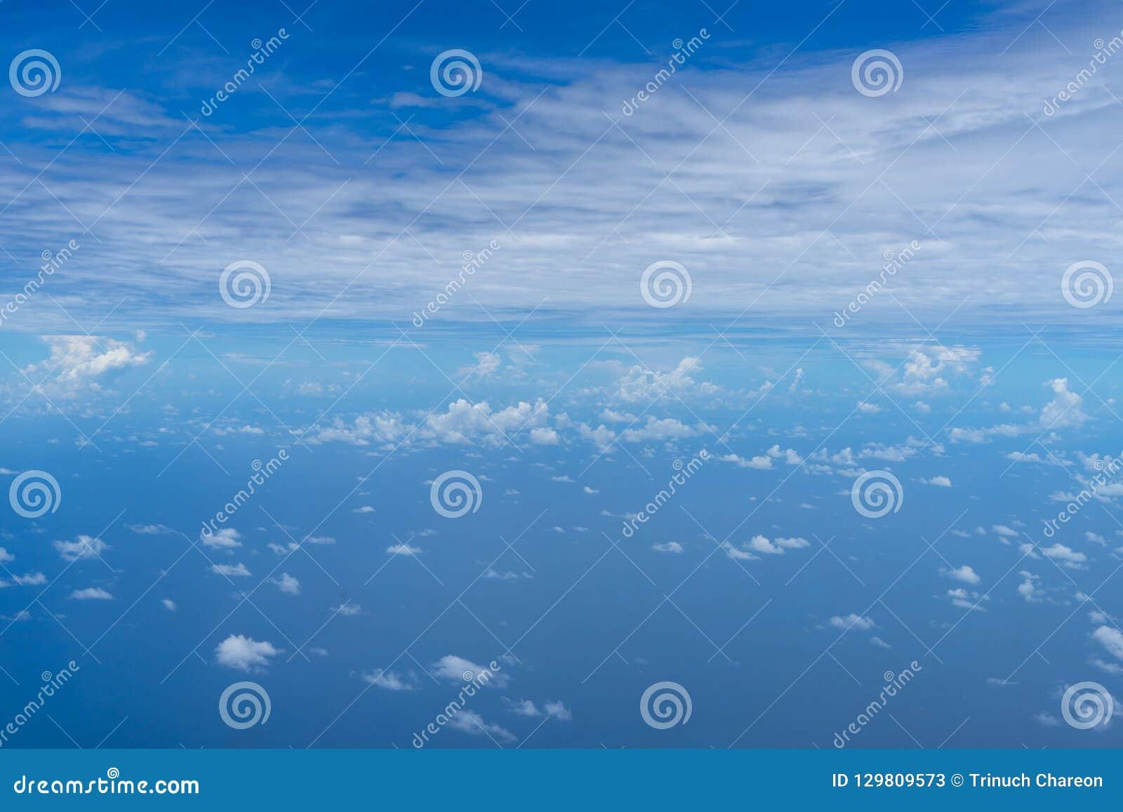 Sikt av det lilla abstrakta vita molnet med den ljusa horisonten för blå himmel och vidsträckt havshavbakgrund från ovannämnt fly