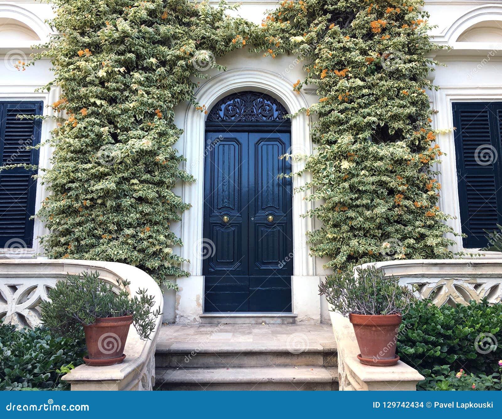 Sikt av en härliga husyttersida och Front Door Seen Det finns fönster på antingen sida av dörren, växter på väggen