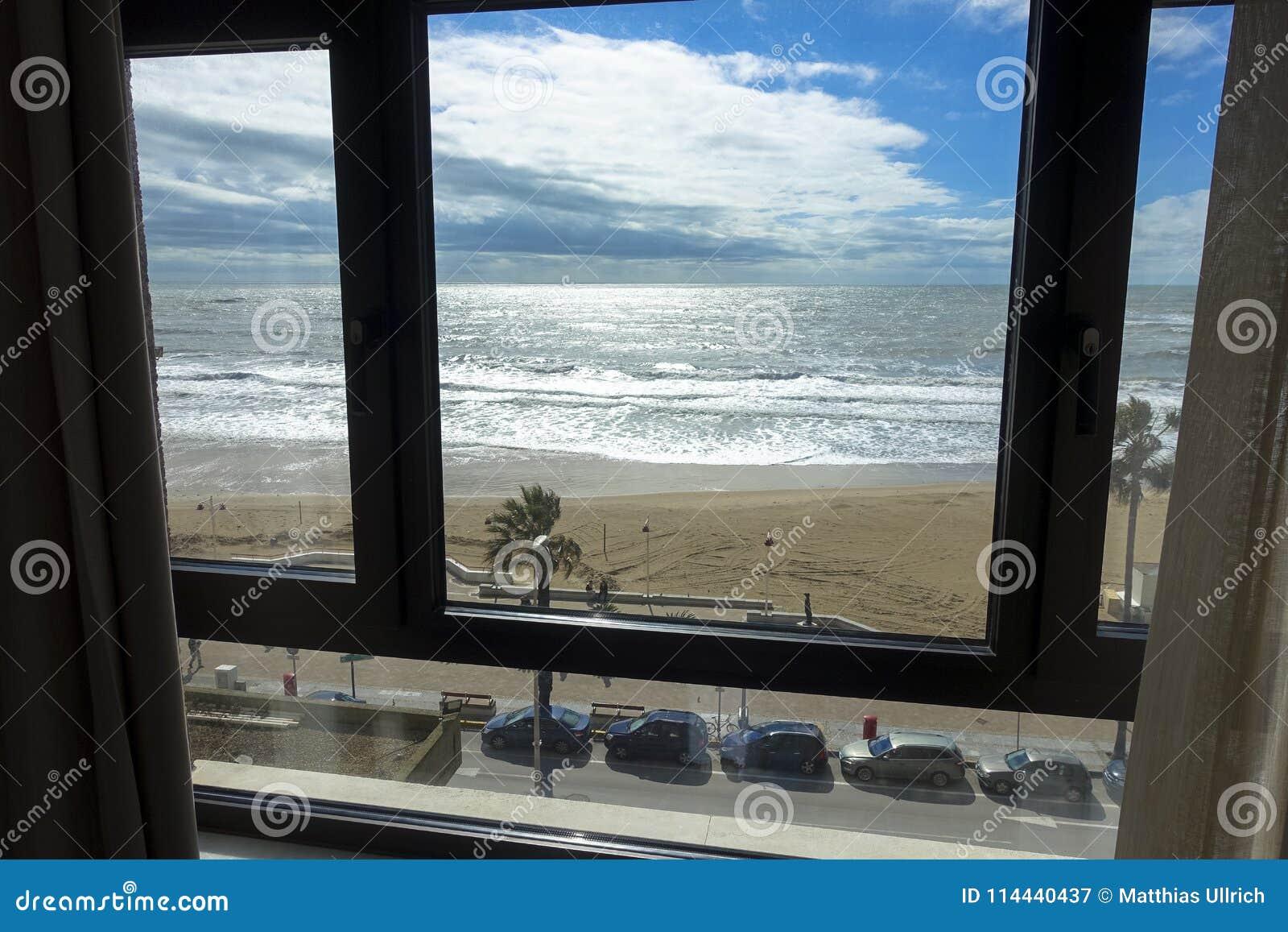 Sikt av ett hotellrumfönster av stranden och havet av Cadiz i Andalusia i Spanien
