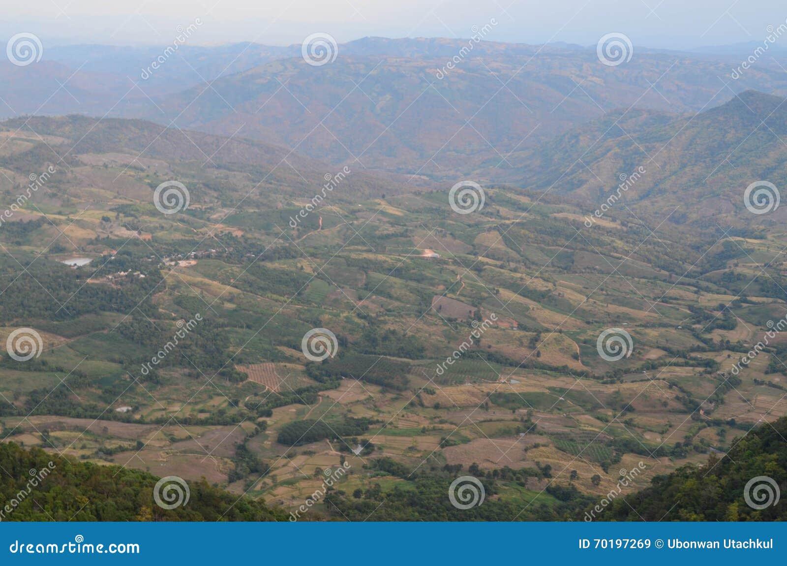 Sikt av fältet och berget - molnig sikt