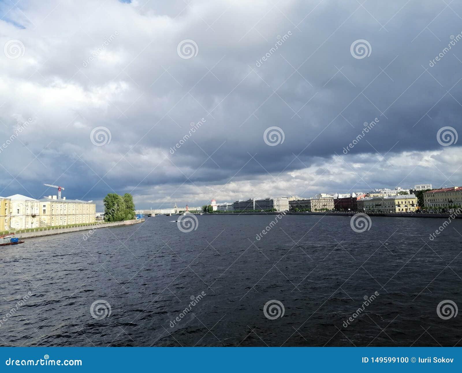 Sikt av floden och byggnaderna mot den dystra himlen och molnen i Petersburg