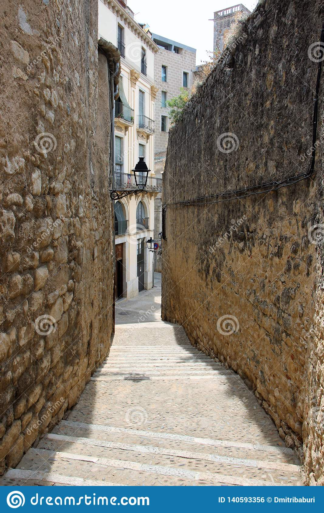 Sikt av gatan mellan de två väggarna i den judiska fjärdedelen av Girona, Spanien