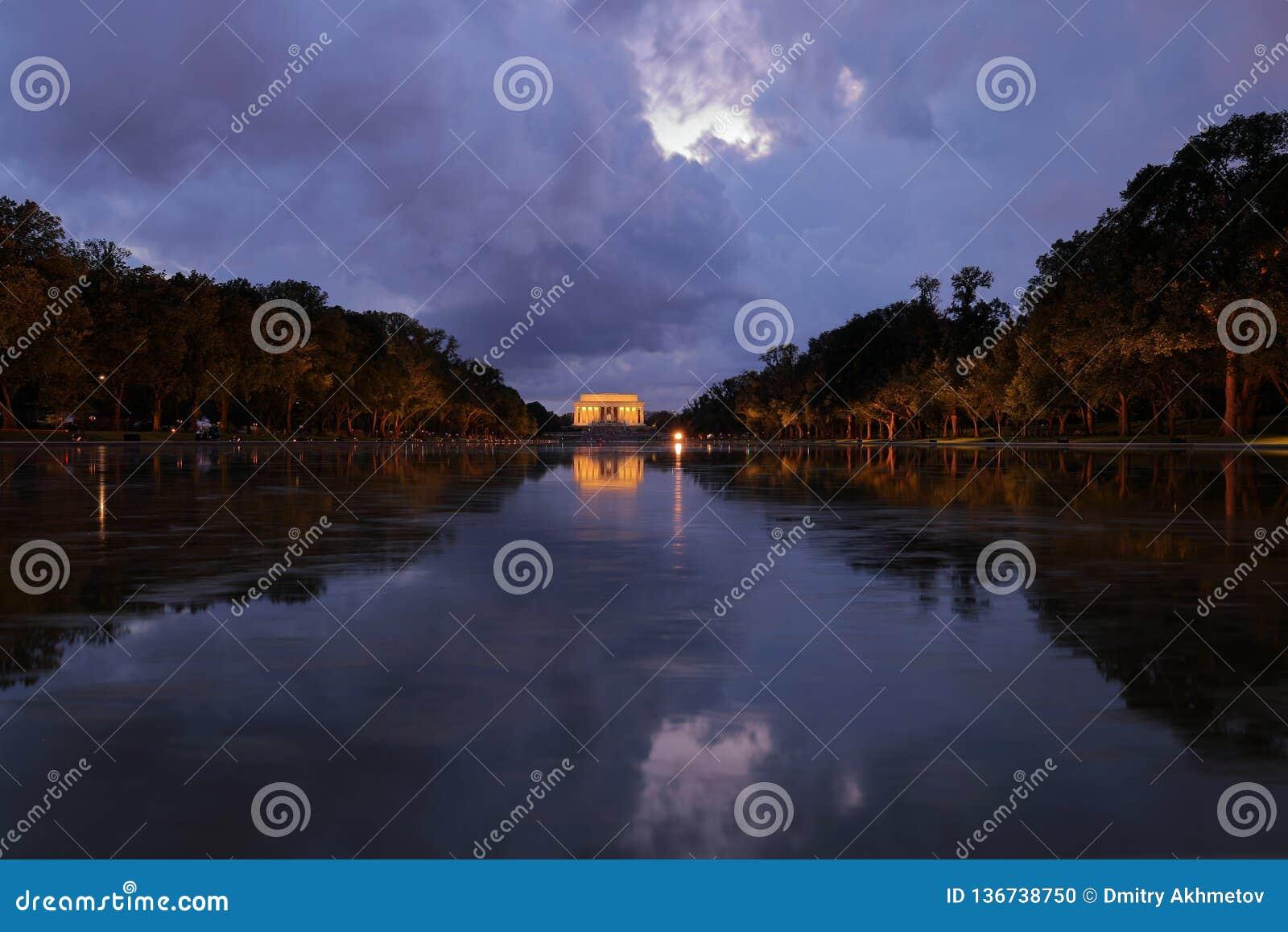 Sikt av Lincoln Memorial och dess reflexion i reflexionspöl på natten med dramatisk himmel