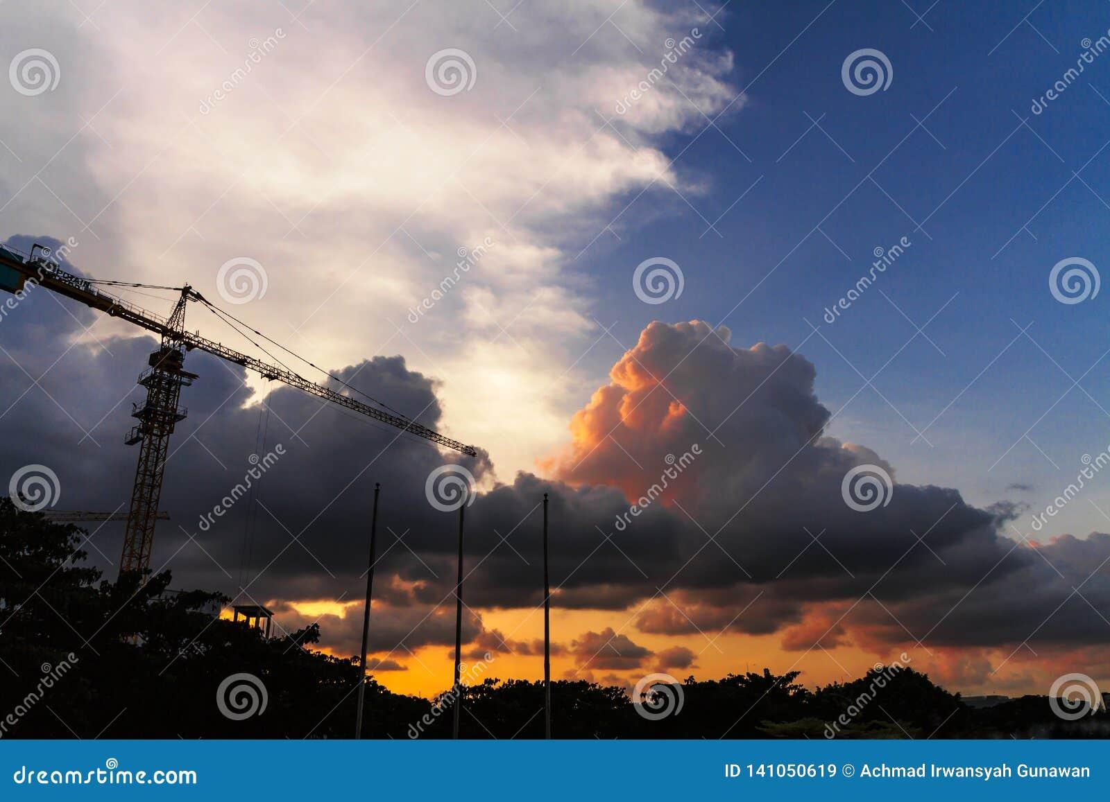 Sikt av molnig himmel på skymning med förgrundskonturn av konstruktionskranen och tre flaggstång