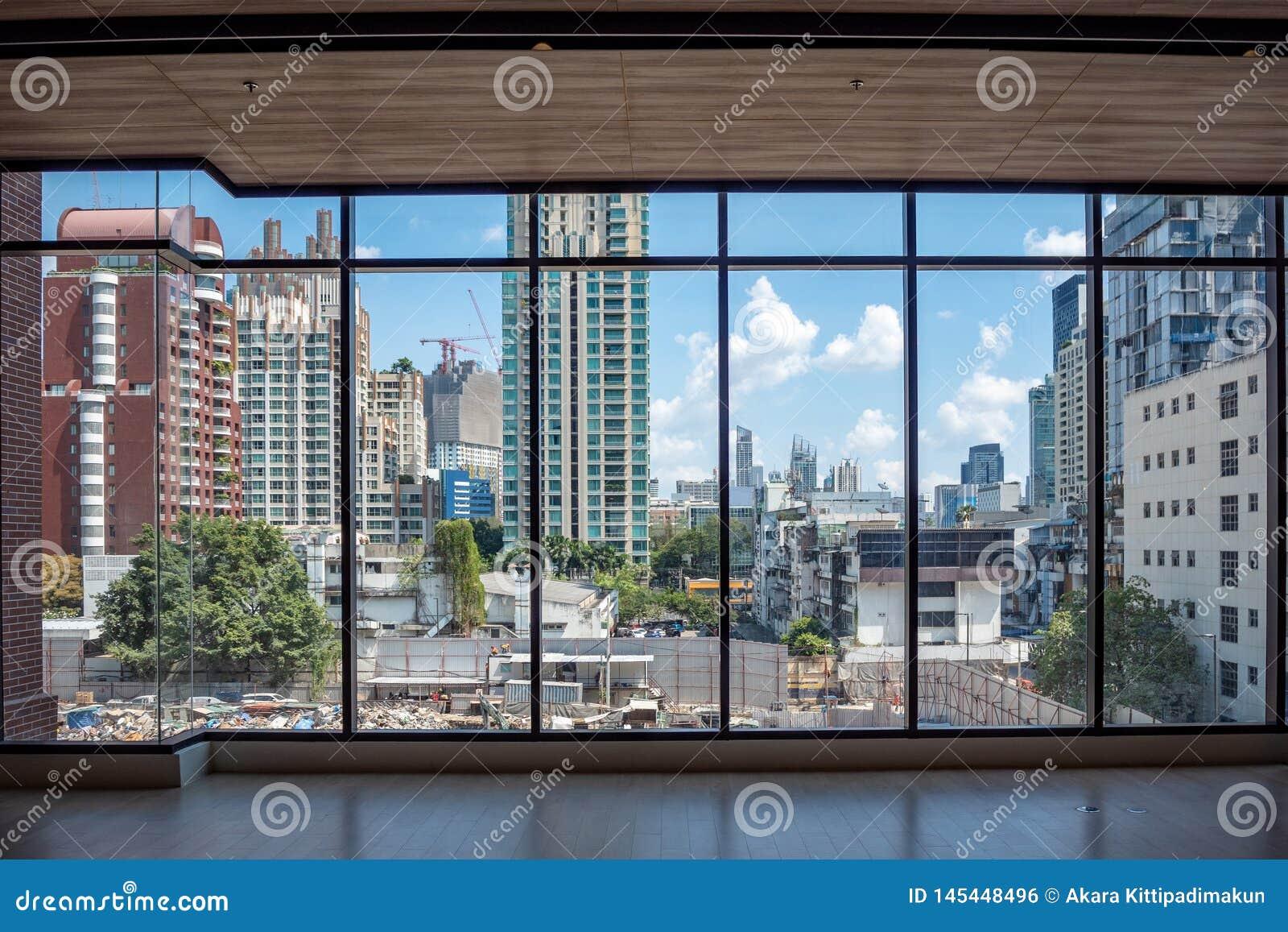 Sikt för affärsområde och för blå himmel för moln från stora exponeringsglasfönster i byggnad