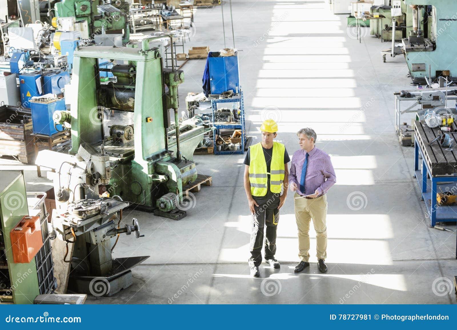Sikt för hög vinkel av den manliga arbetsledaren och manuella arbetaren som har diskussion i metallbransch
