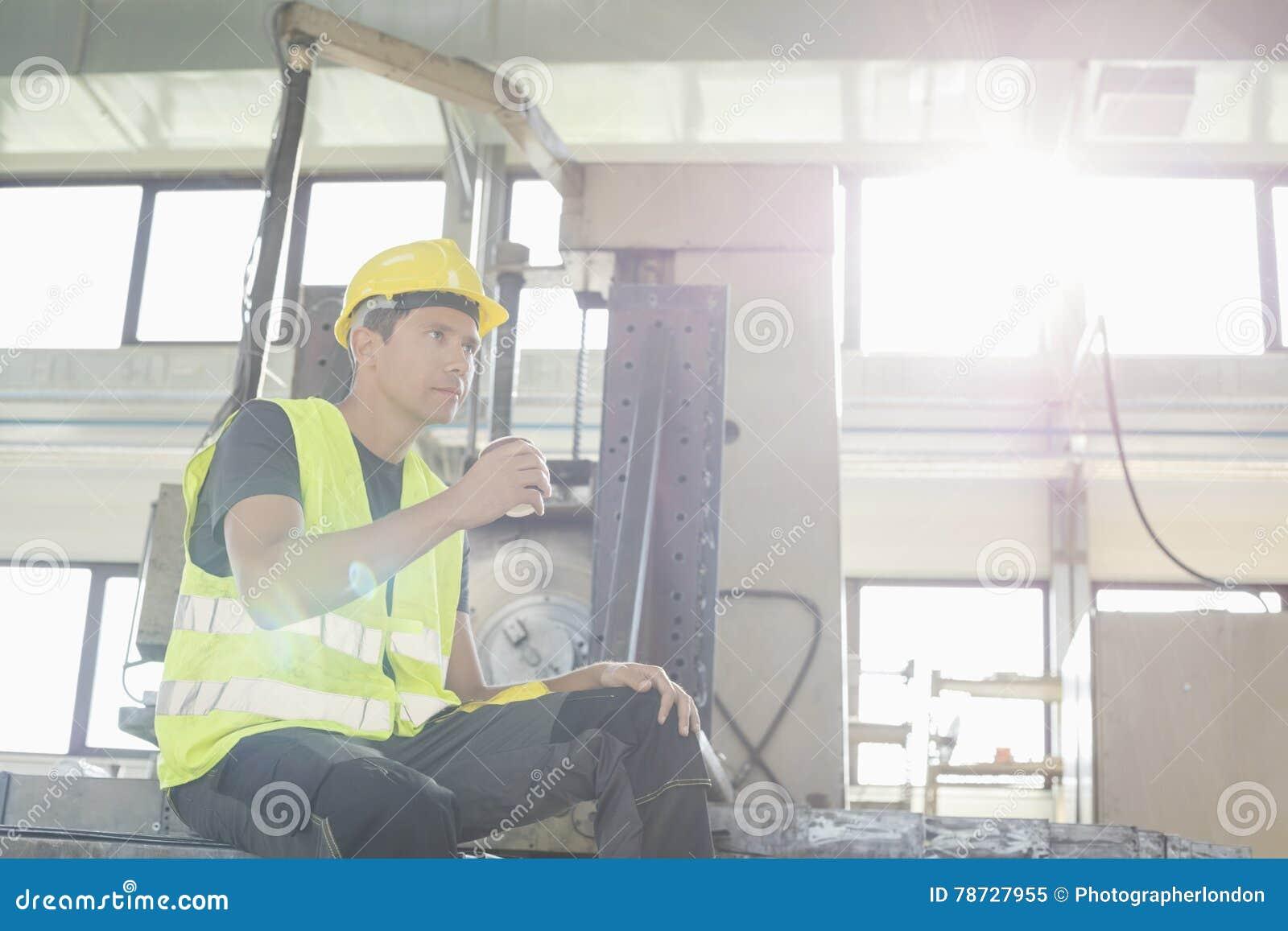 Sikt för låg vinkel av den mitt- vuxna manuella arbetaren som har kaffe i metallbransch