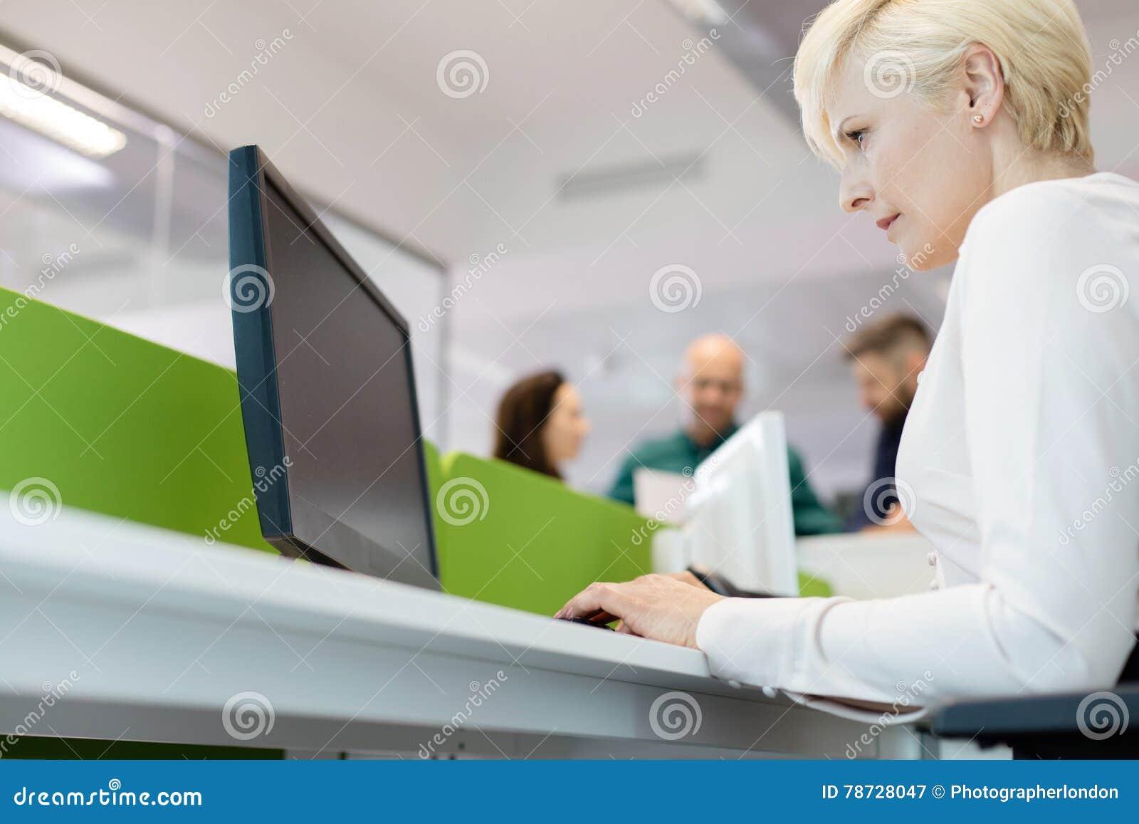 Sikt för låg vinkel av den mogna affärskvinnan som använder datoren med kollegor i bakgrund på kontoret