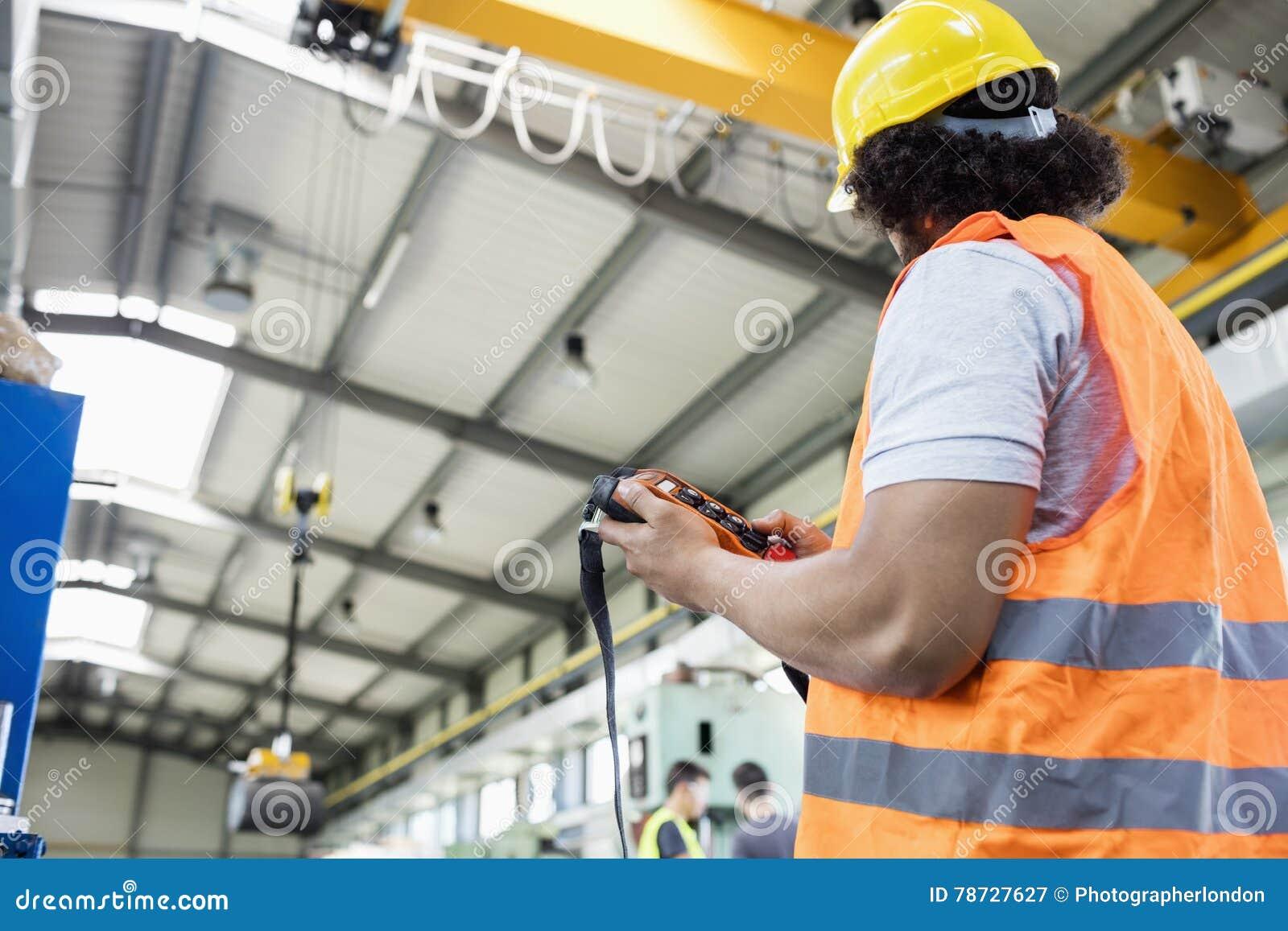 Sikt för låg vinkel av den unga fungeringskranen för manuell arbetare i fabrik