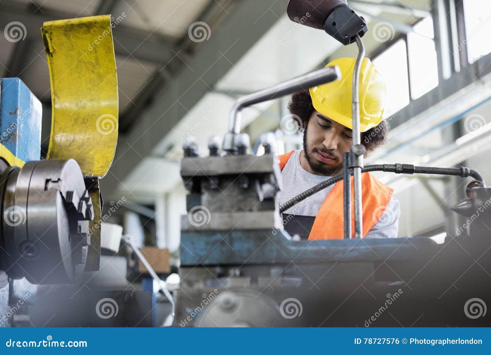 Sikt för låg vinkel av den unga manuella arbetaren som arbetar på maskineri i metallbransch