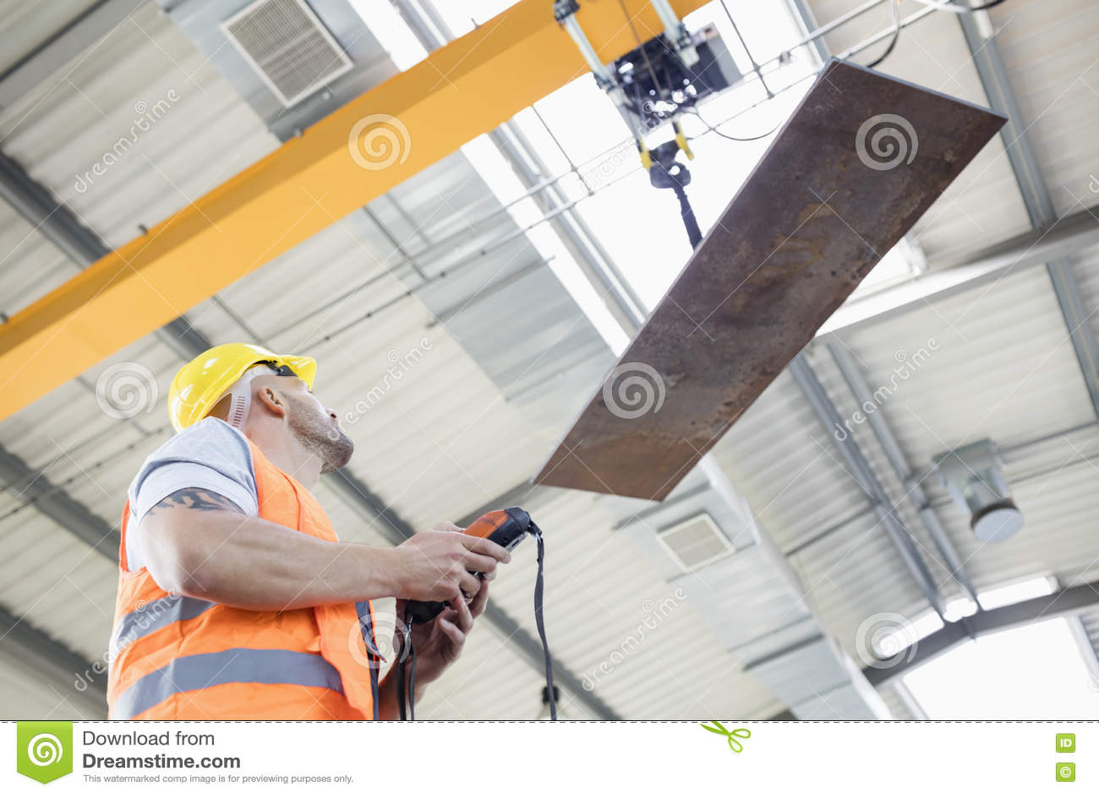 Sikt för låg vinkel av för fungeringskran för manuell arbetare metall för ark lyftande i bransch