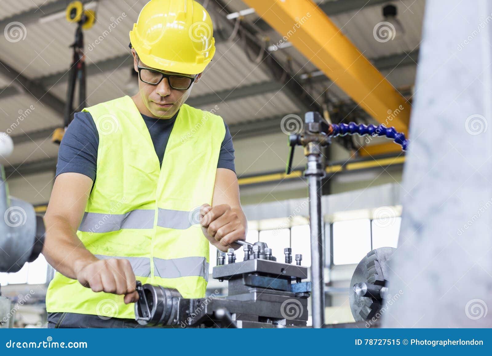 Sikt för låg vinkel av fungerande maskineri för mitt- vuxen arbetare i metallbransch