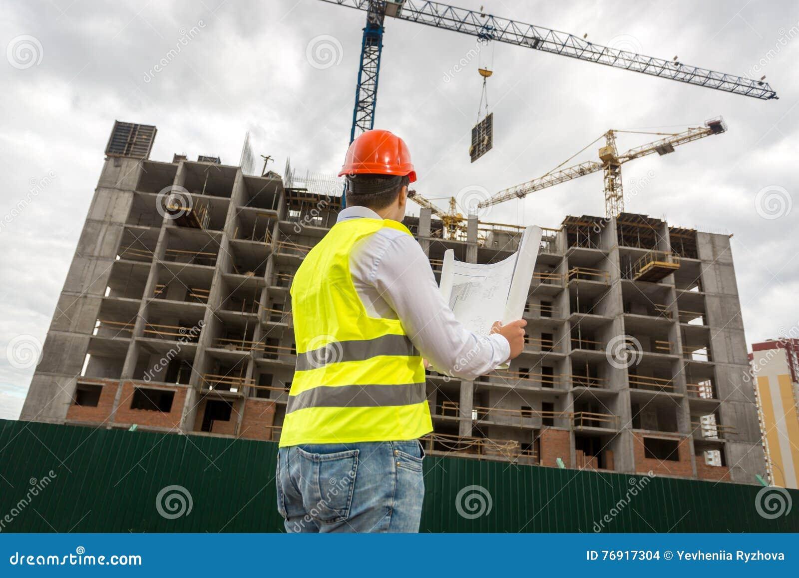 Sikt från baksida på inspektören som ser byggnad under constructi