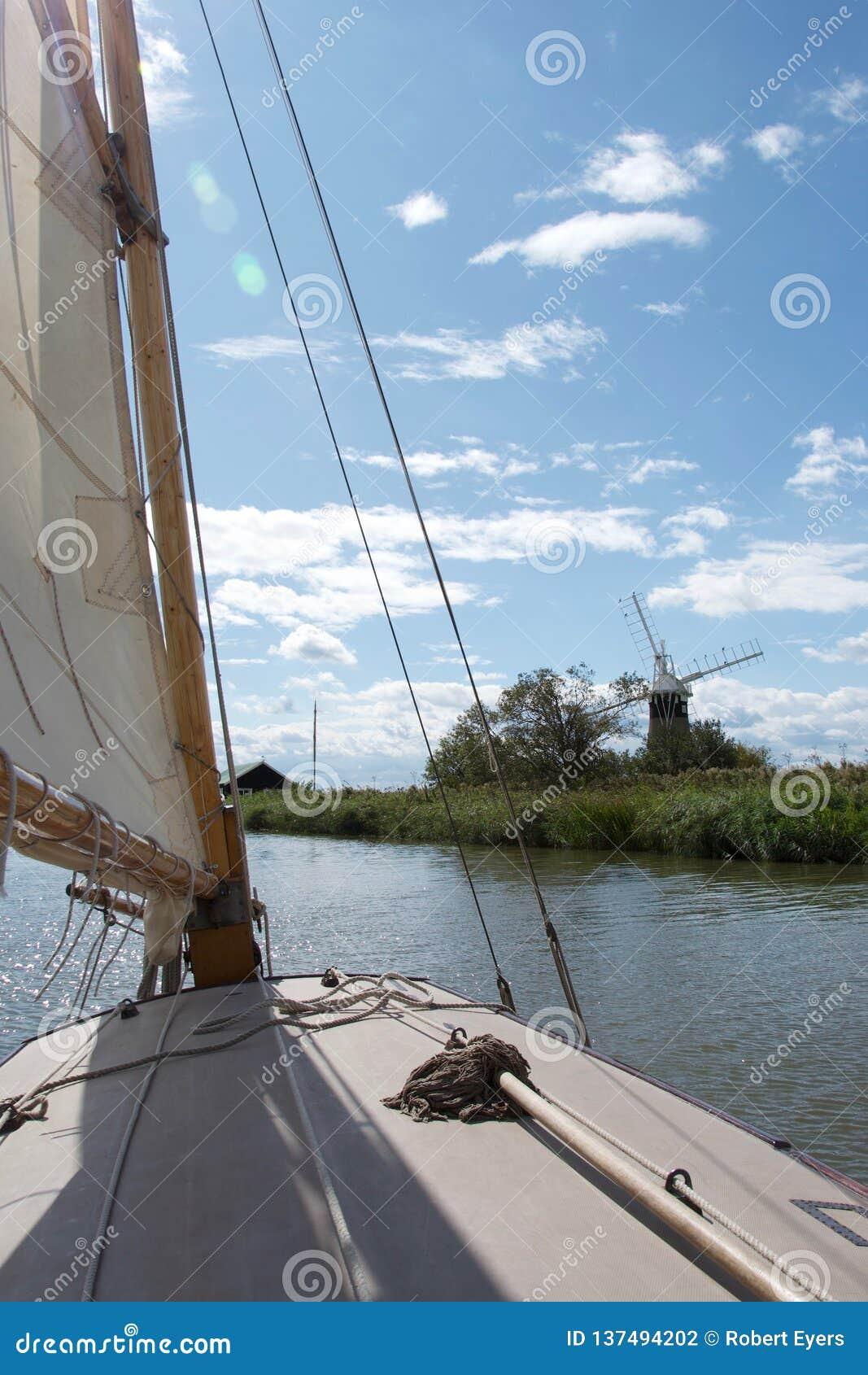 Sikt från en segelbåt nära en väderkvarn-/vindpump på den Norfolk sjödistrikt i Norfolk