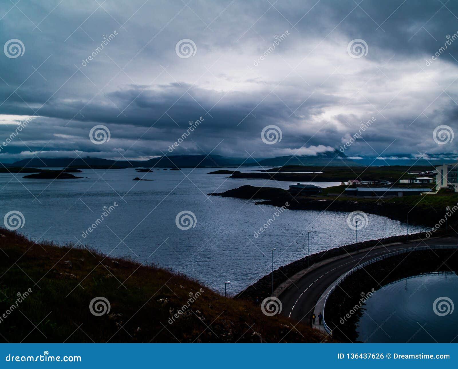 Sikt från fyrön av Stykkishà ³lmur, Island med couldy väder på havet och en väg