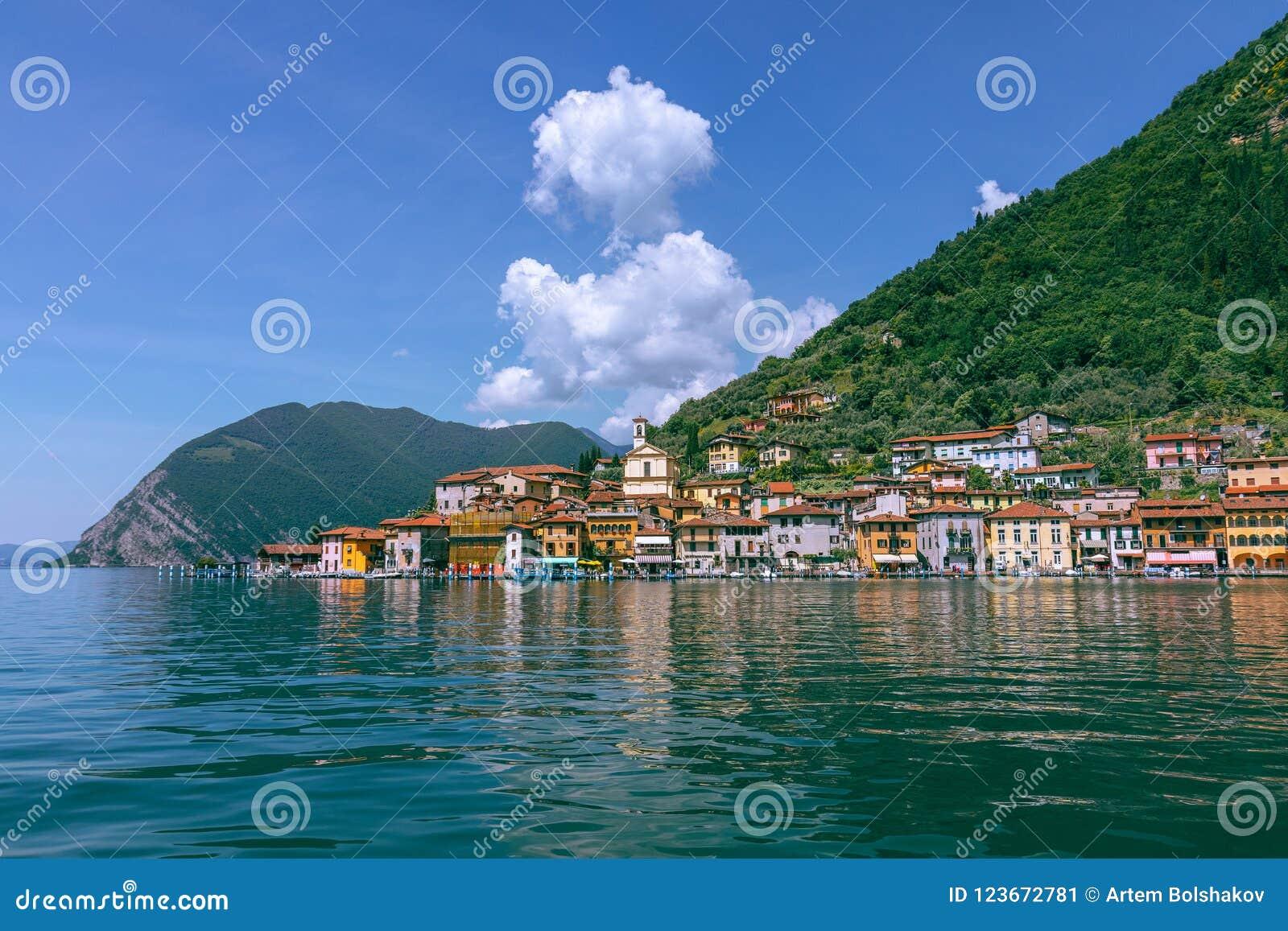 Sikt från sjön av Iseo på lilla staden av Sulzano