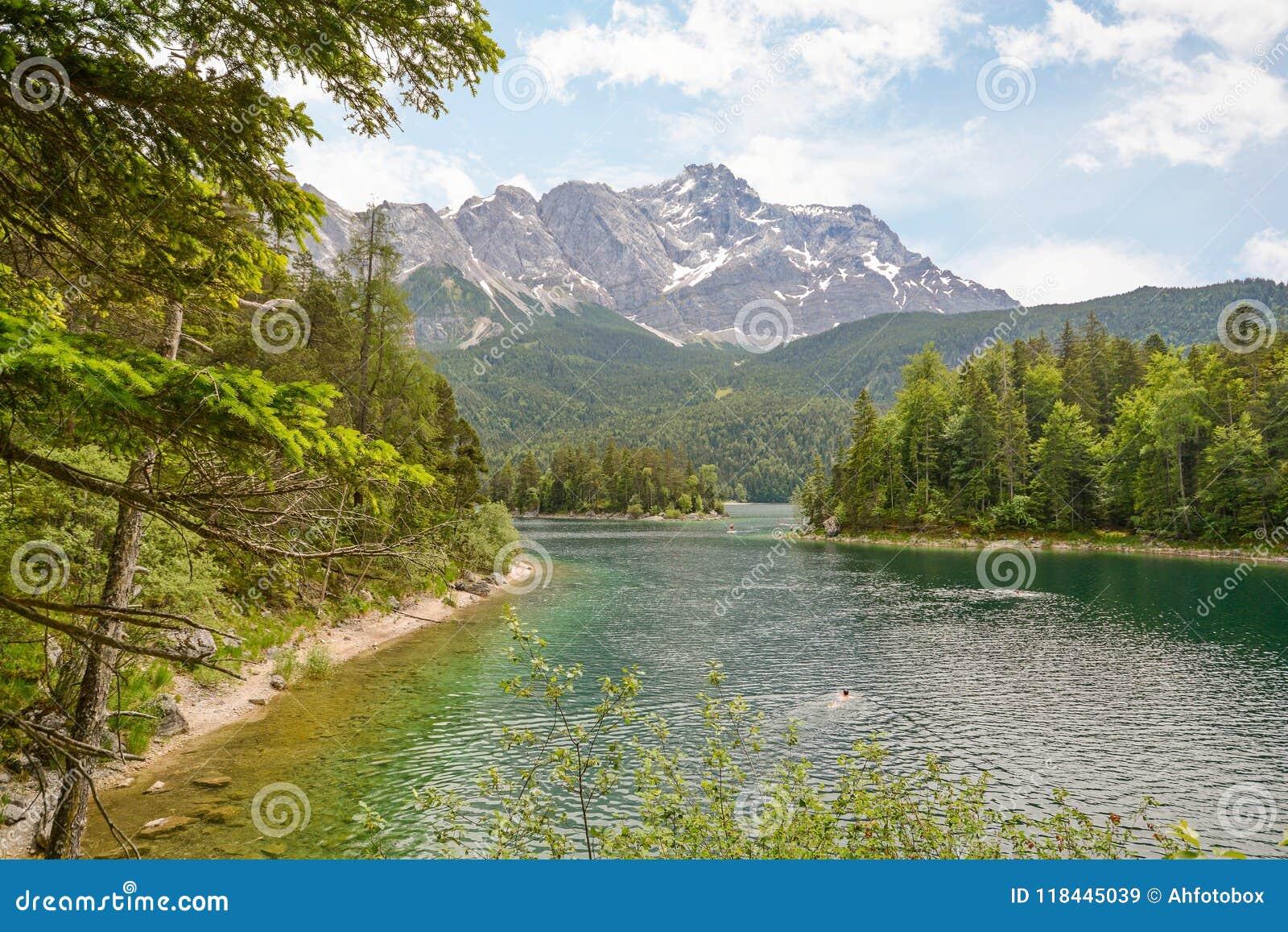 Sikt till sjön Eibsee och Zugspitze, högst berg för Tyskland` s Tyskland i för bavarianfjällängarna, Bayern
