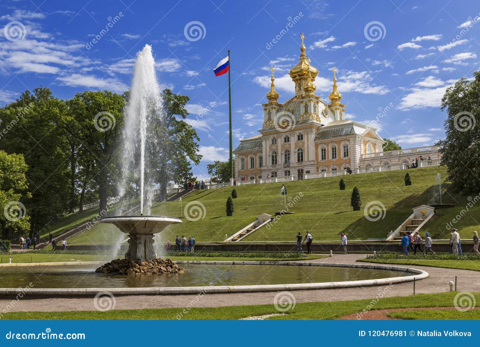 Sikten av bunkespringbrunnfranskan och slottkyrkan av Peter och Paul i det lägre parkerar av Peterhof, St Petersburg,