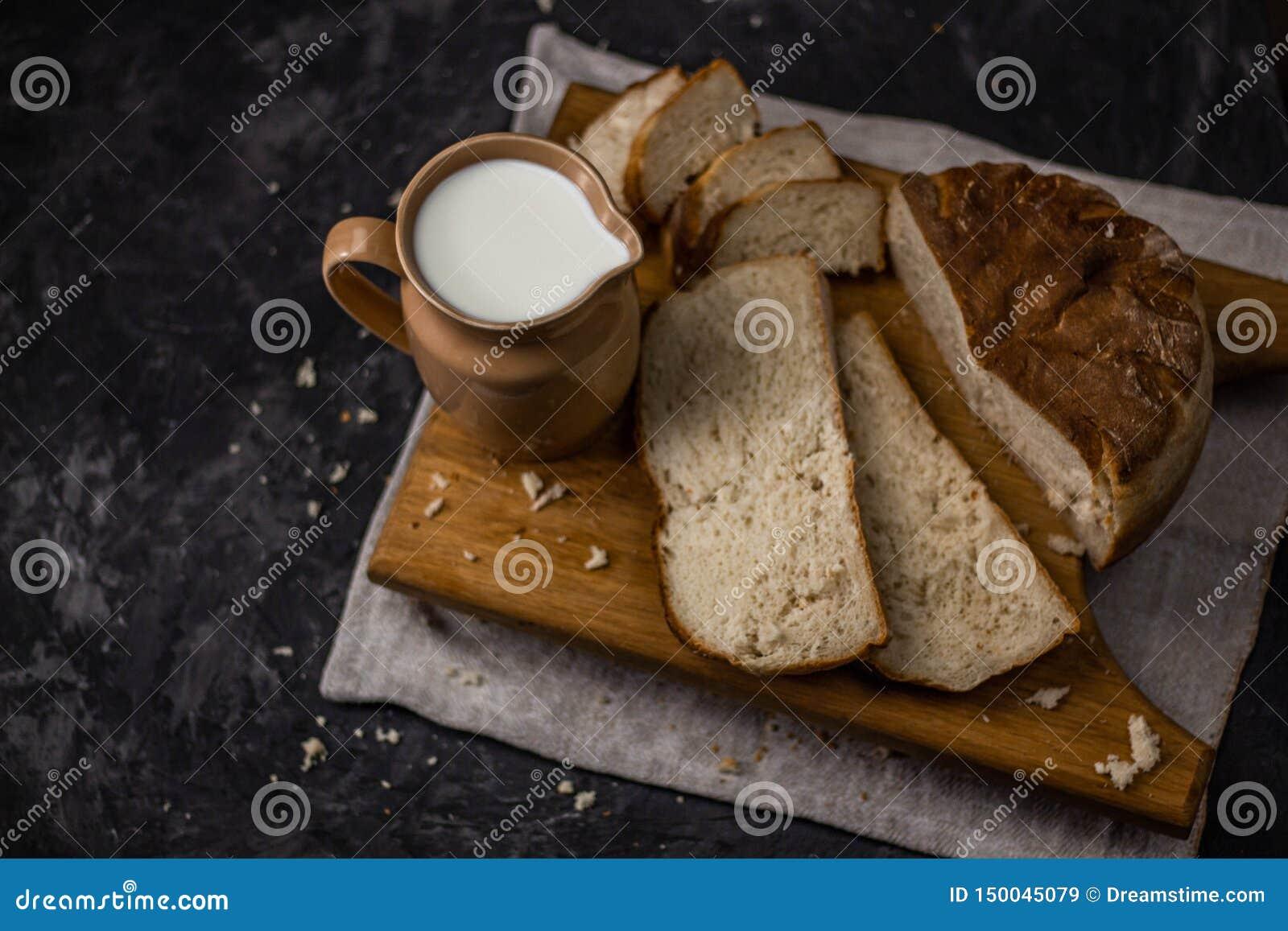 Sikten av en tillbringare av mjölkar och hemlagat nytt bakat vitt bröd på en svart bakgrund