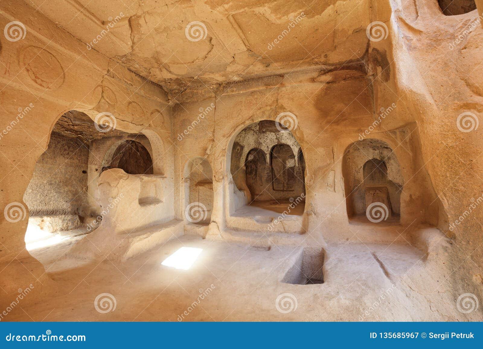 Sikten av fördärvar av lokalen av den forntida kyrkan i de gamla grottasandstenarna i dalarna av Cappadocia