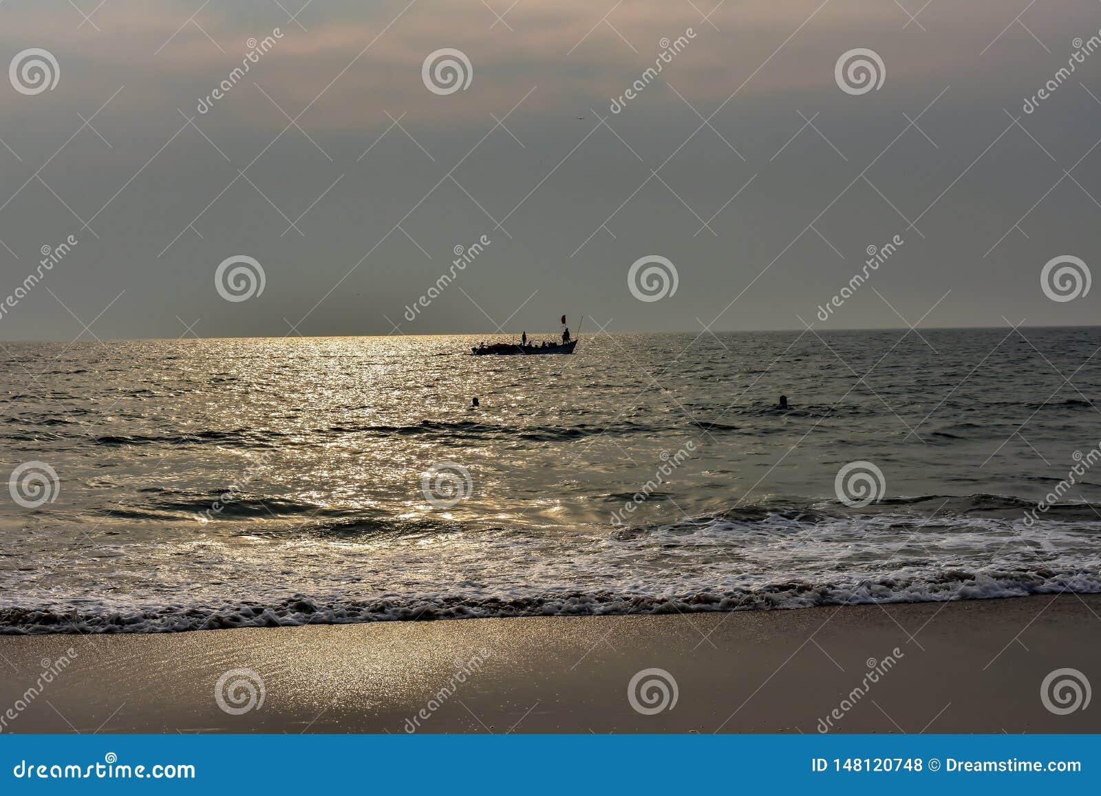 Sikten av refraktionen av guld- solsken i havsstranden med konturn av ett fartyg skapade en magisk bakgrund