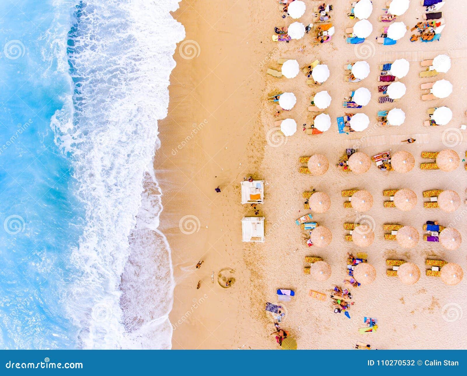 Sikten för ögat för ` s för solstol- och paraplyfågeln på sand sätter på land i Grekland