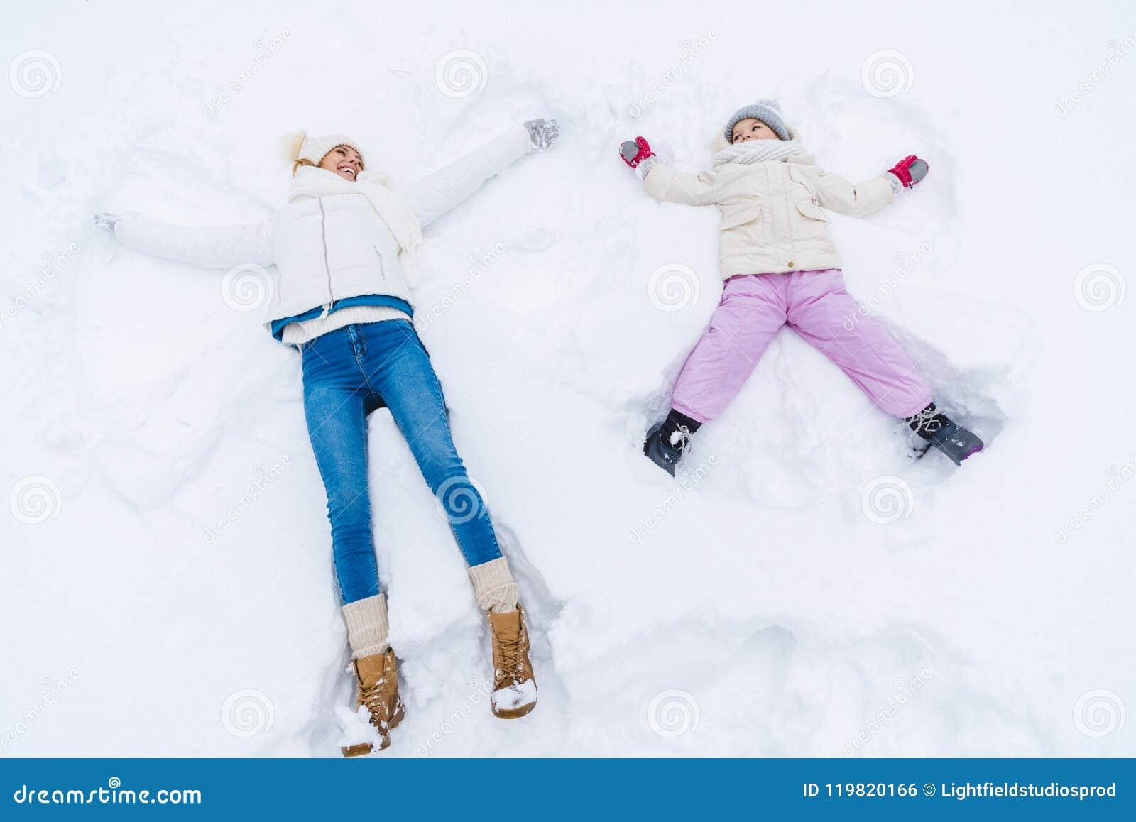 Sikten för den höga vinkeln av lycklig moder- och dotterdanande snöar änglar och att le