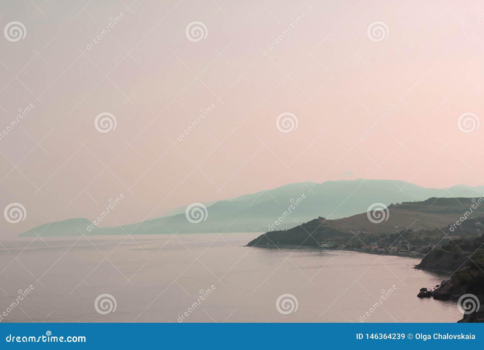 Sikten fr?n h?jden av berget i havet p? solnedg?ngen