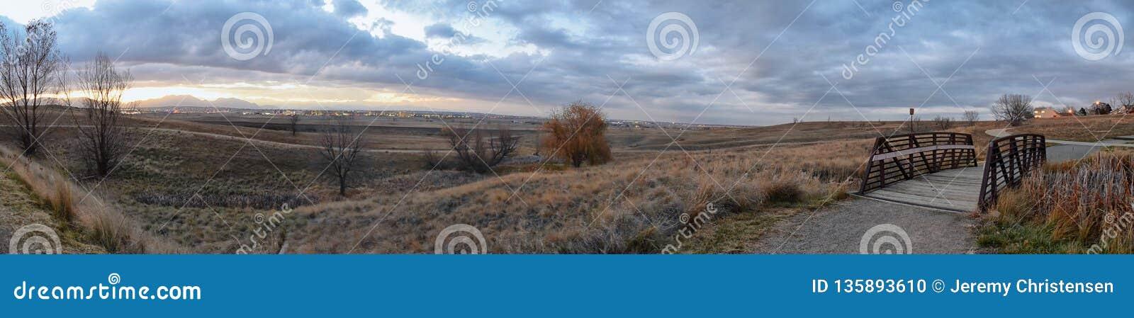 Sikter av den gå banan för Josh's damm, den reflekterande solnedgången i Broomfield Colorado som omges av Cattails, slättar och