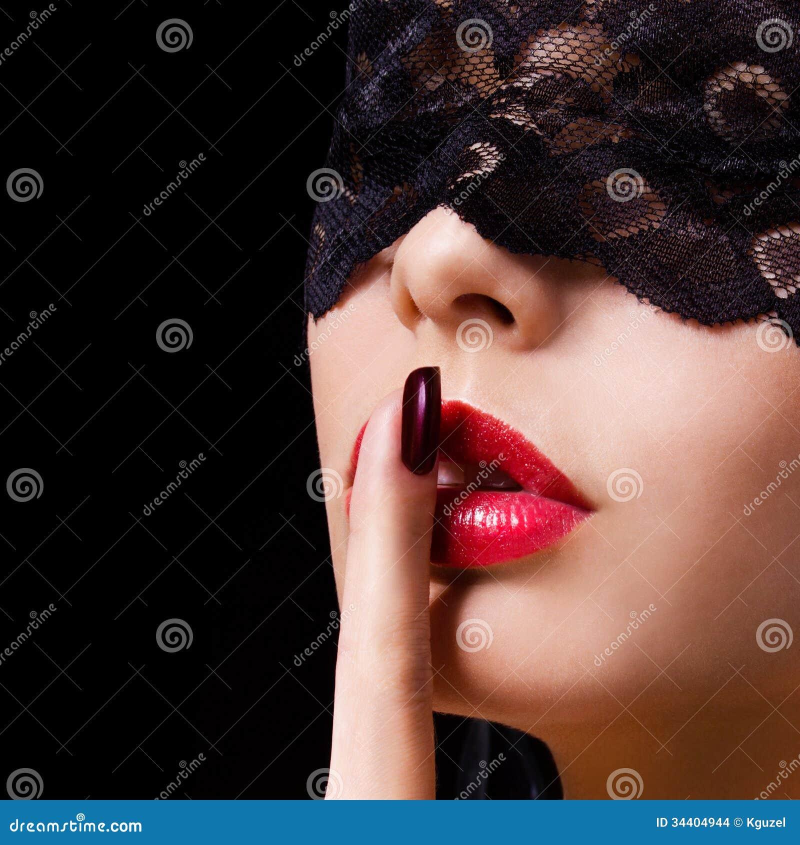 Silêncio. A mulher  sexy  com o dedo em seu mostrar vermelho dos bordos cala. Menina erótica com máscara do laço sobre o preto