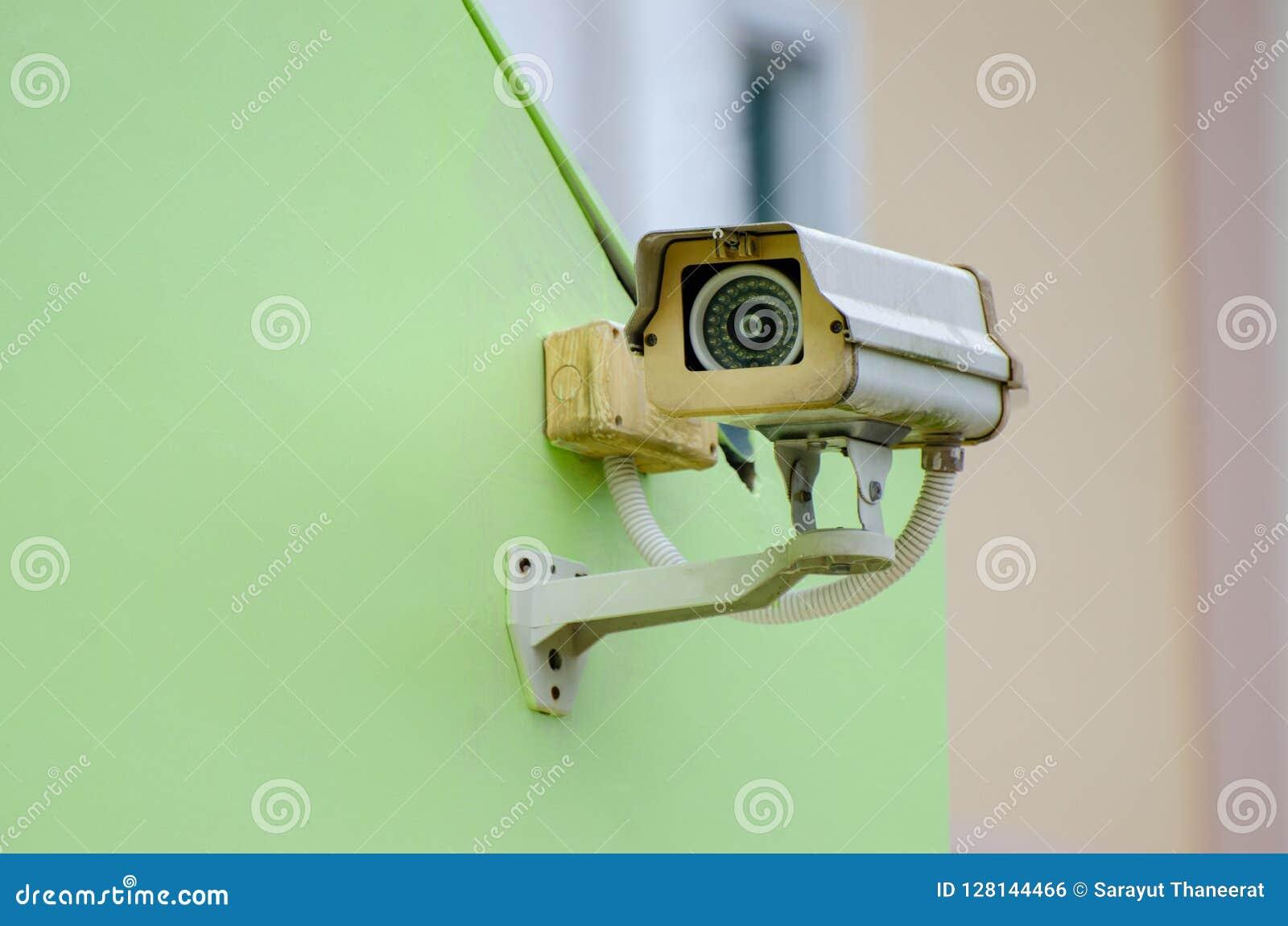 Silberne Überwachungskamera auf der grünen Wand Videoüberwachungskamera auf grünem Hintergrund