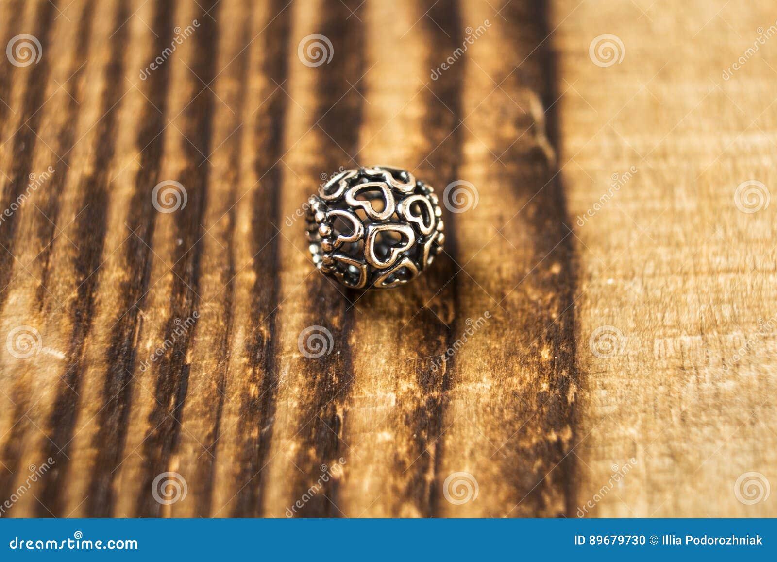 Silberne Perle für Armband auf hölzernem Hintergrund