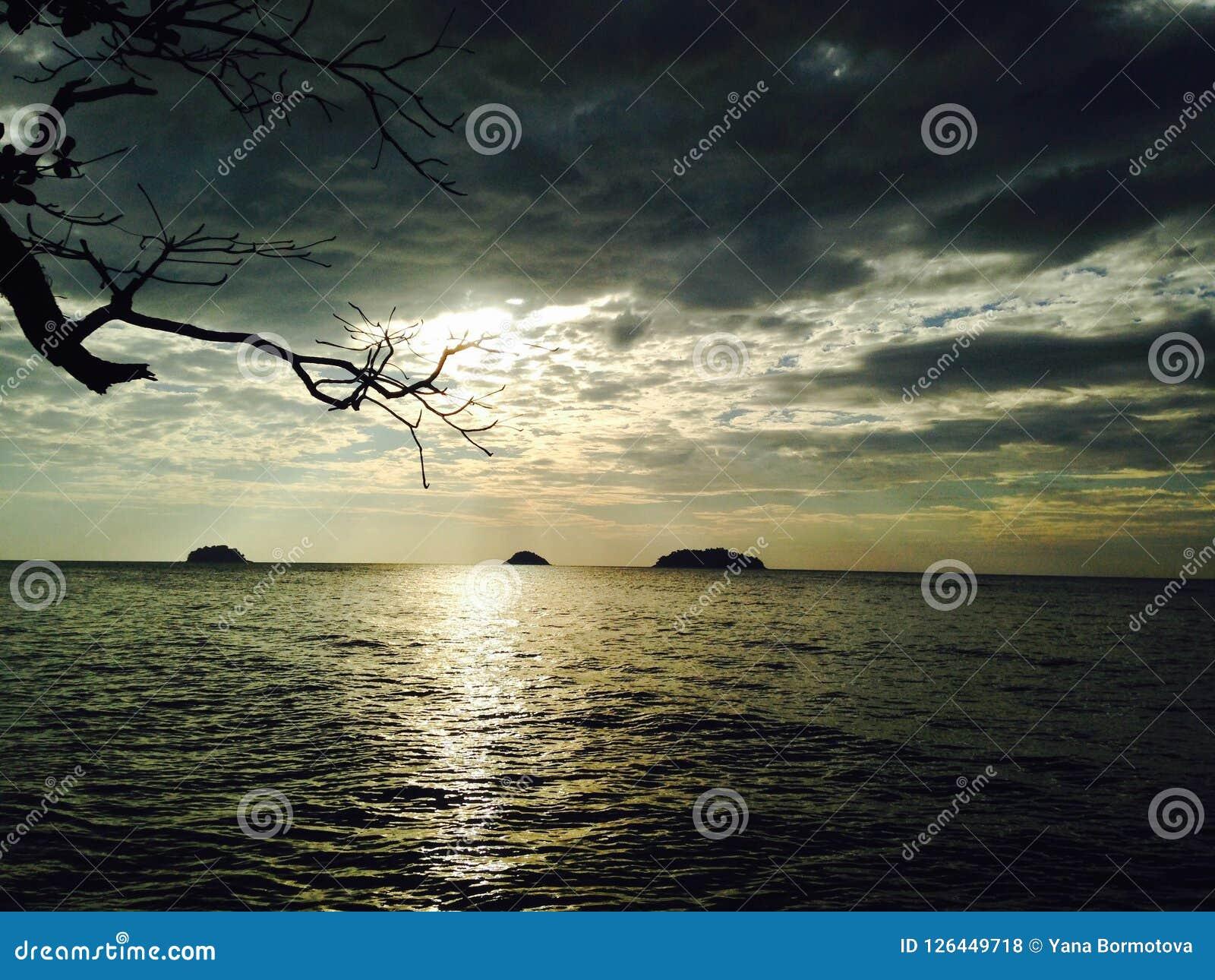 Silberner Sonnenuntergang über dem Meer, sonnen das Glänzen durch die Wolken