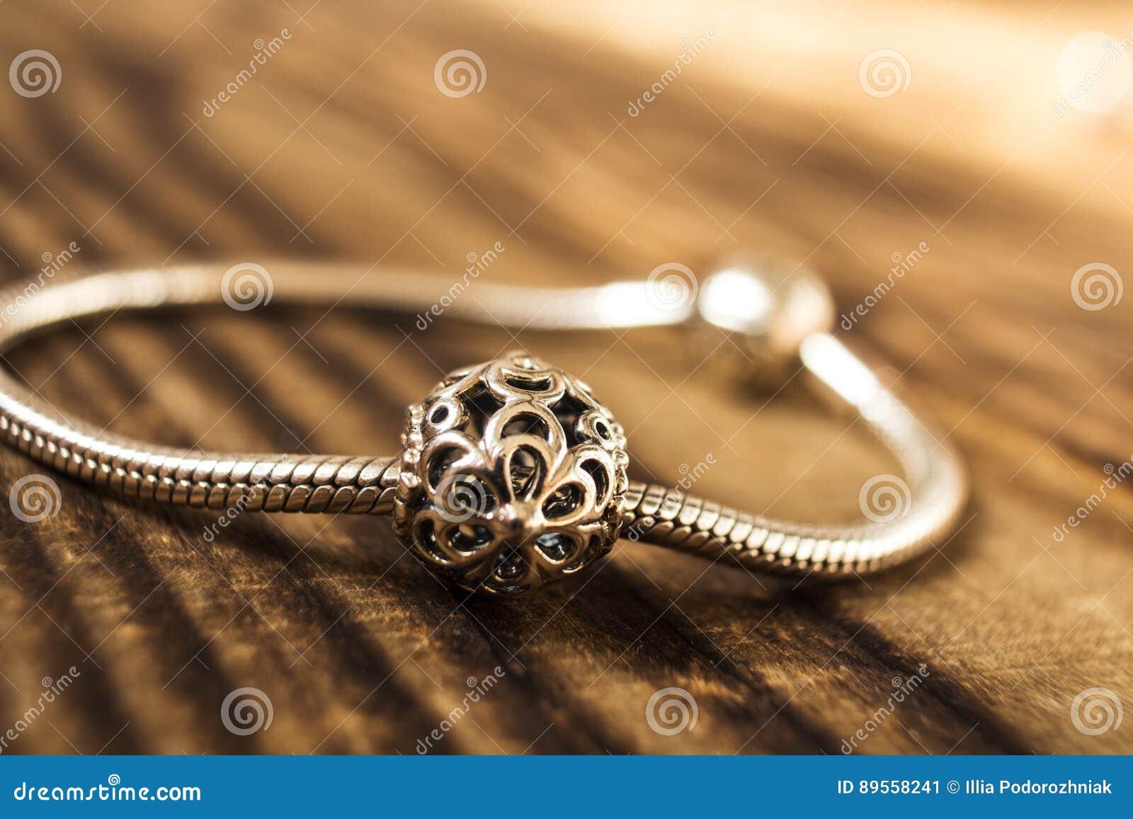 Silbernes Armband mit silberner Perle auf hölzernem Hintergrund