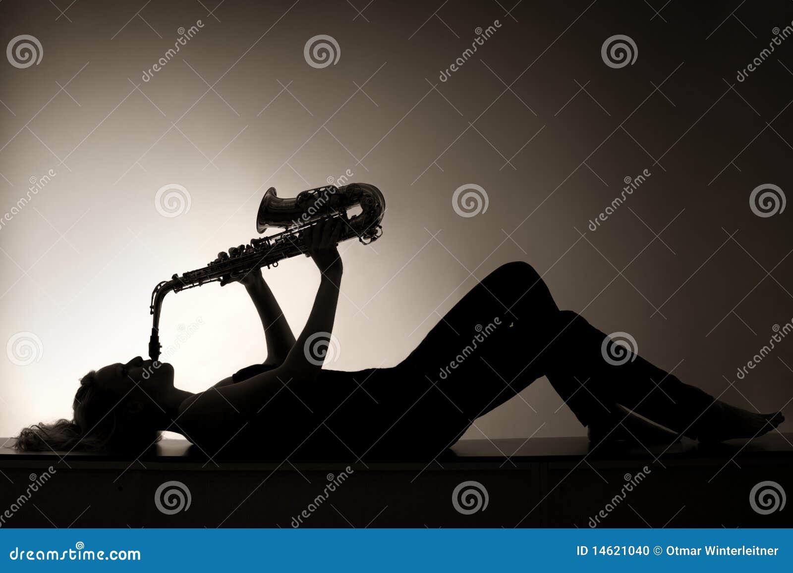 Silhouet dat van vrouw het spelen saxofoon ligt