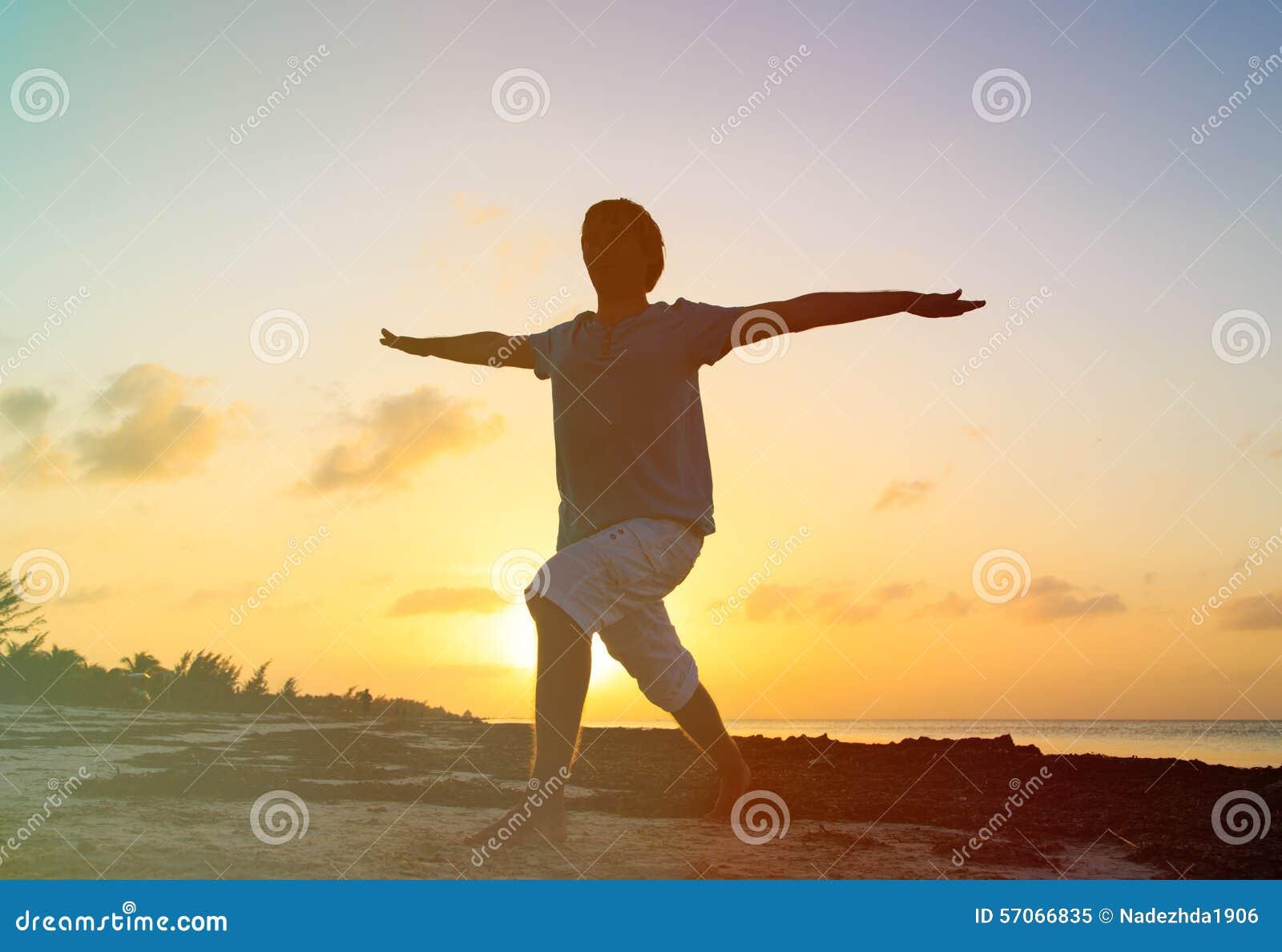 Silhouet die van de jonge mens yoga doen bij zonsondergang